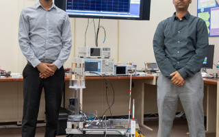 U.S. Army Research Laboratory scientists Dr. Fikadu Dagefu (left) and Gunjan Verma (right) pose with one of the robots used to validate a new algorithm they developed, which enables localization of humans and robots indoors or in areas with many obstacles